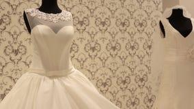 Close-up do manequim com vestido de casamento, mulher bonita nova que escolhe um vestido branco em uma loja do casamento video estoque