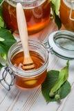 Close up do mel em um frasco e nas folhas do cal Fotografia de Stock Royalty Free