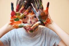 Close up do menino com cara e mãos na pintura fotografia de stock