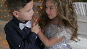 Close-up do menino e da menina em um fundo da árvore de Natal crianças em equipamentos bonitos vídeos de arquivo