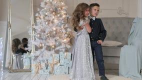 Close-up do menino e da menina em um fundo da árvore de Natal crianças em equipamentos bonitos filme