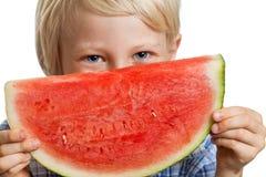 Close-up do menino que espreita sobre a melancia Fotografia de Stock