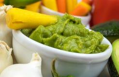 Close up do mergulho do Guacamole cercado por vegetais e por ingredientes coloridos Fotografia de Stock