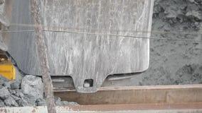 Close-up do minério da carga da cubeta da máquina escavadora no caminhão do descarga-corpo Sector mineiro filme