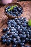 Close-up do mirtilo fresco e brilhante em uma caixa de madeira Obscuridade saudável, madura, crua e brilhante - bagas azuis em um imagens de stock