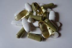 Close up do montão de comprimidos verdes, brancos e amarelos fotografia de stock