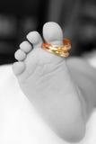 Close up do pé dos bebês com dois anéis dourados Imagem de Stock
