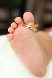 Close up do pé dos bebês com dois anéis dourados Fotos de Stock