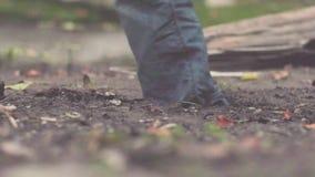 Close-up do pé na lama estoque Close-up do pé do homem nas sapatilhas e nas calças de brim, imergido profundamente na lama durant vídeos de arquivo