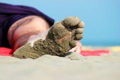Close-up do pé de um homem de sono que encontra-se na praia Imagem de Stock