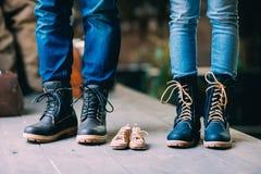 Close-up do pai, da mãe e dos pés pequenos futuros do filho nas sapatas Foto de Stock Royalty Free