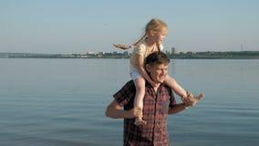 Close-up do pai e da filha que jogam junto Um pai novo está girando sua filha na praia da costa de mar video estoque