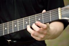 Close up do pescoço da guitarra com jogo do guitarrista Fotos de Stock Royalty Free