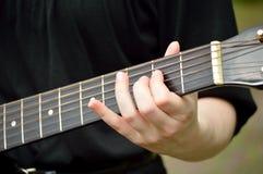 Close up do pescoço da guitarra com jogo do guitarrista Foto de Stock