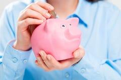 Close-up do porco e das moedas do mealheiro imagens de stock royalty free