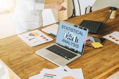 Close-up do portátil com análise estatística da inscrição na tela na tabela de madeira Estão próximo os gráficos de papel Imagens de Stock Royalty Free