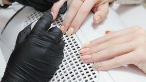 Close-up do processo do tratamento de mãos no salão de beleza Trabalhos do manicuro nos pregos do cliente vídeos de arquivo