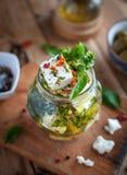 Close-up do queijo de feta posto de conserva no azeite, nas ervas e nos flocos de pimenta vermelha no fundo de madeira imagens de stock