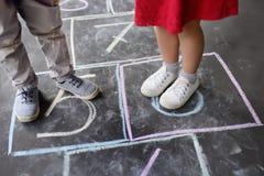 Close up do rapaz pequeno e os pés e as amarelinhas da menina tirado no asfalto Criança que joga amarelinha o jogo no ar livre do fotografia de stock royalty free