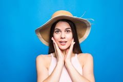 Close up do retrato do chapéu de palha vestindo surpreendido da mulher com mãos nos mordentes isolados sobre o fundo azul imagem de stock