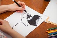 Close up do retrato do ` s da mulher do desenho na mesa foto de stock