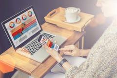 Close-up do smartphone com gráficos, cartas, diagramas, dados em uma tela nas mãos da mulher de negócios nova que sentam-se na ta Foto de Stock Royalty Free