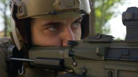 Close up do soldado das forças especiais que olha seu alvo e que prepara-se para atear fogo filme