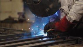Close-up do soldador durante o trabalho com construção do metal em uma loja da fábrica vídeos de arquivo