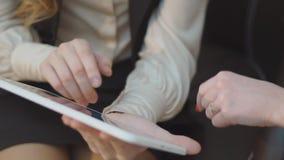 Close-up do tablet pc nas mãos fêmeas No fundo, no foco macio, duas jovens mulheres Meninas que compram em linha, trabalhando filme
