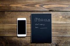 Close-up do telefone celular e do caderno com o texto: Entrega da pizza tabela de madeira do fundo Preto do caderno com branco imagens de stock