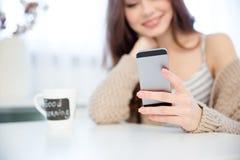 Close up do telefone celular usado pela jovem mulher feliz Imagem de Stock