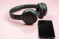Close-up do telefone esperto com fones de ouvido em um fundo cor-de-rosa imagem de stock royalty free