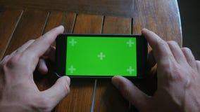 Close-up do toque masculino das mãos do smartphone na cozinha Chave verde do croma da tela filme