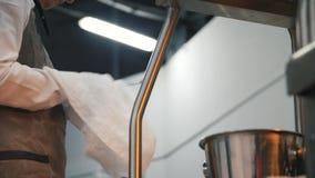 Close-up do trabalhador da cozinha em um avental branco que limpa colheres em um caf? ou em um restaurante Metragem conservada em filme
