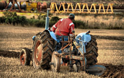 Close-up do trator e de Ploughing Fotografia de Stock Royalty Free