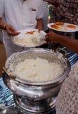 Close up do vendedor de alimento indiano da rua que serve o arroz cozinhado da bacia fotografia de stock