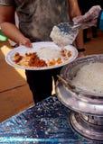 Close up do vendedor de alimento indiano da rua que serve o arroz cozinhado da bacia imagem de stock