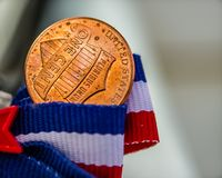 Close-up do verso da cauda da moeda de um centavo na fita vermelha, branca e azul foto de stock