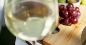 Close-up do vidro e dos frutos de vinho branco na tabela vídeos de arquivo