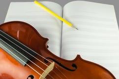 Close up do violino, da folha vazia da nota e do lápis Foto de Stock