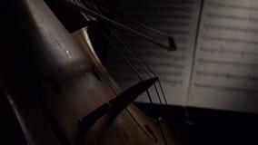 Close up do violoncelo com as folhas das notas Fim acima Vista lateral filme