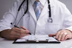 Close-up Of A Doctor Analyzing Report royalty free stock photos