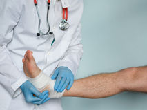 Close up of doctor bandaging one injured foot after an accident Royalty Free Stock Images