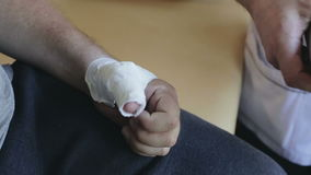 Close up. Doctor is bandaging a patient thumb. stock footage
