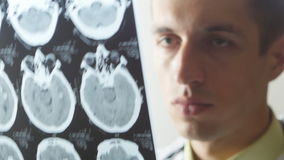 Close up of Doctor examines a snapshot of magnetic resonance imaging. Portrait of a doctor with a syringe