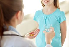 Close up of doctor giving medicine to happy girl Royalty Free Stock Photo