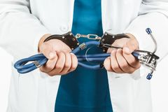 Close-up Of Doctor Hands With Stethoscope In Handcuffs. Stock Photo