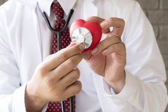 Close up doctor hands with stethoscope. And red heart royalty free stock photo