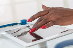 Close-up Of Doctor hans  on  Digital Tablet At Desk with stethoscope Royalty Free Stock Photo