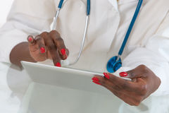Close-up Of Doctor hans  on  Digital Tablet At Desk with stethoscope Stock Photo